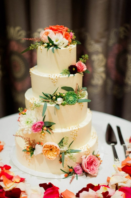 tall white cake accessorized with flowers and succulents