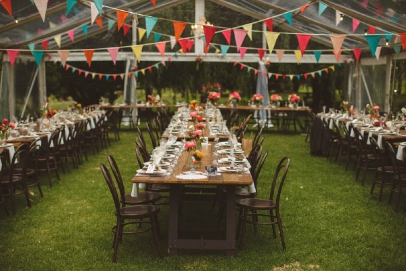 Colorful wedding tent reception bunting farm tables