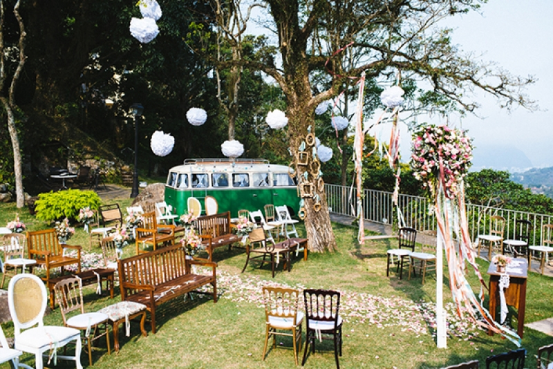 Eclectic backyard wedding ceremony different chairs hanging poufs