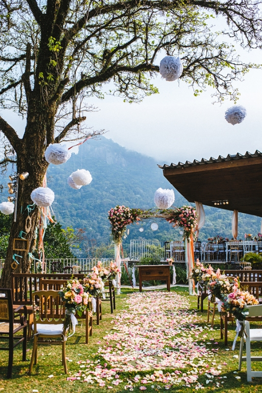 Eclectic backyard wedding ceremony aisle flower petals hanging poufs