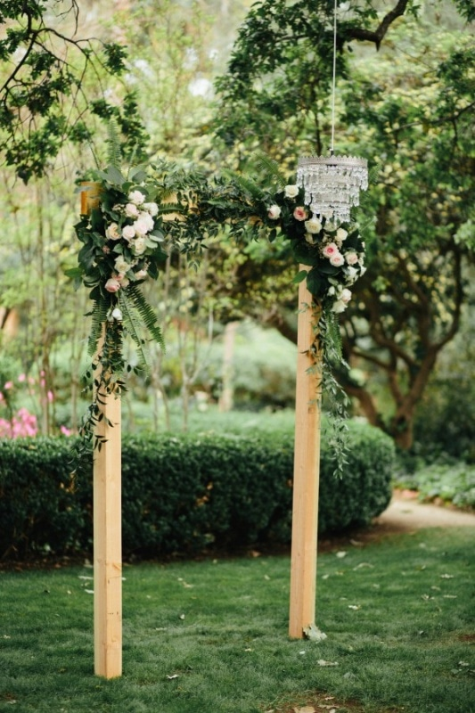 Simple Wooden Ceremony Arch with Flowers and Leaves, Hanging Chandelier