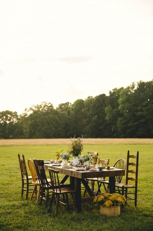 outdoor reception with wooden table and chairs