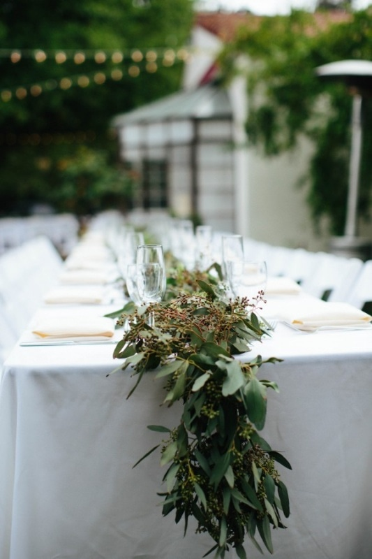 understated reception decor with leaf garland and white table settings