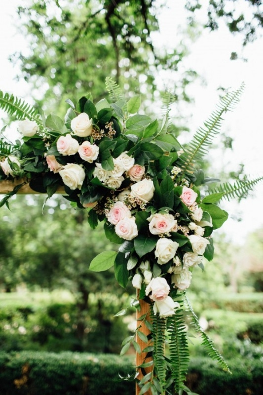 ceremony arch with light pink floral design and ferns