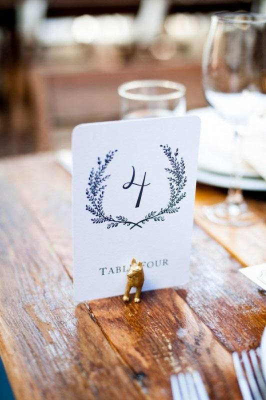paper table number with quirky gold painted animal holder