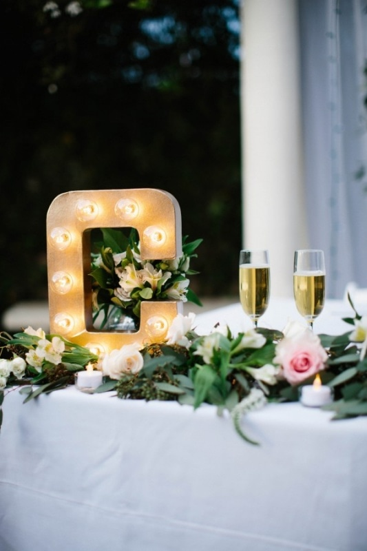letter marquee and leaf garland on newlyweds table