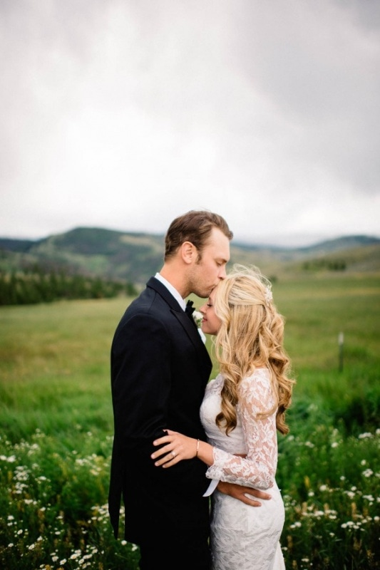 sweet couple portrait with groom kissing bride's forehead