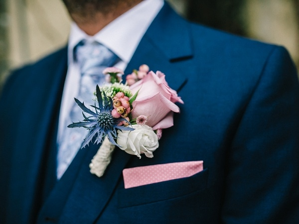 pink rose boutonniere with blue and ivory flowers on a navy suit