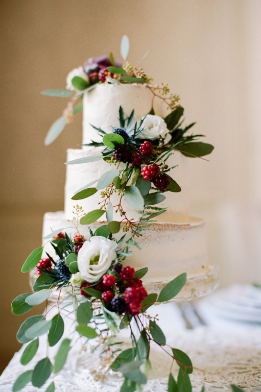partially iced three tier wedding cake with eucalyptus and berries