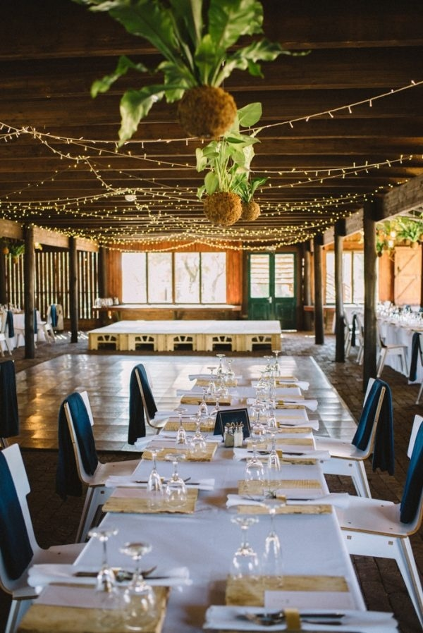 Organic and Rustic Barn Reception with Hanging Plants and Twinkle Lights