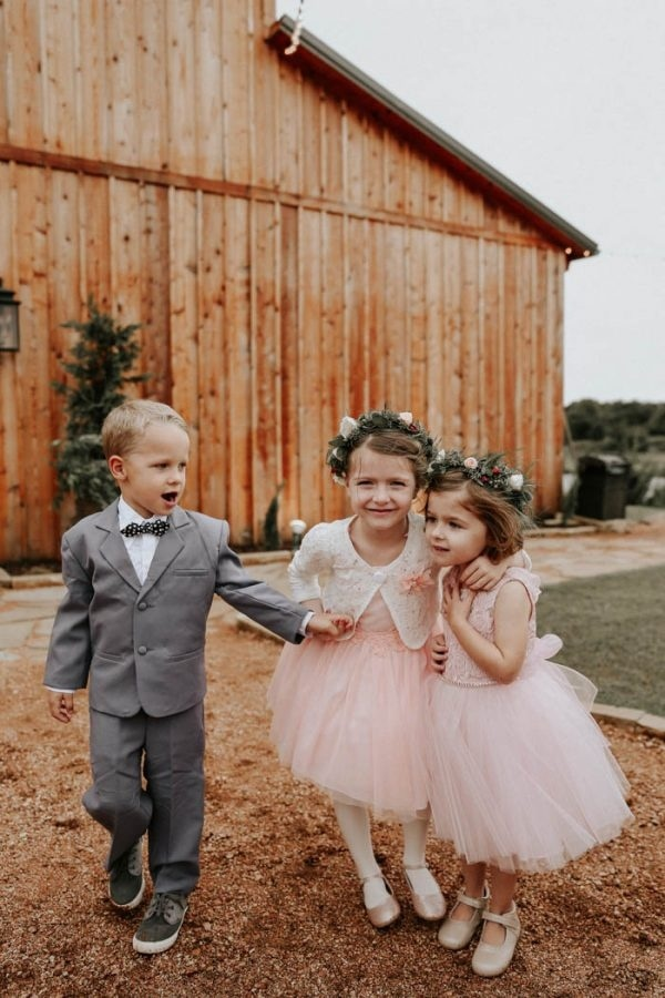 Ring Bearer in Grey and Flower Girls in Blush Outside a Barn
