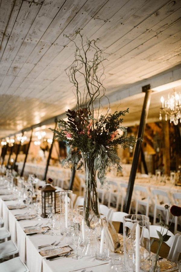 Barn Reception Table Setting with Lanterns, Clear Glass Vases, and Tall Floral Arrangements