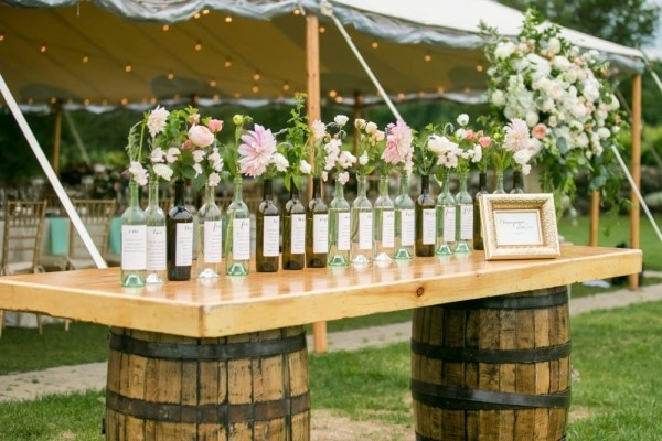 Rustic Wine Bottle Floral Display on Wine Barrels