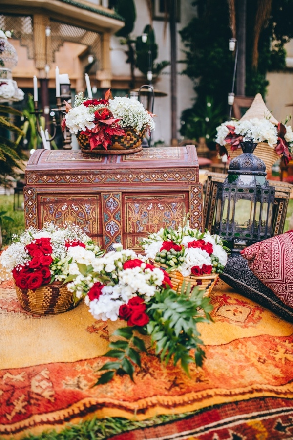 Moroccan Wedding Decor With Red Florals Lanterns And Rugs