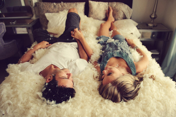 adorable engagement photo of couple laying in bed of down feathers - photo by top Florida wedding photographer Jason Mize