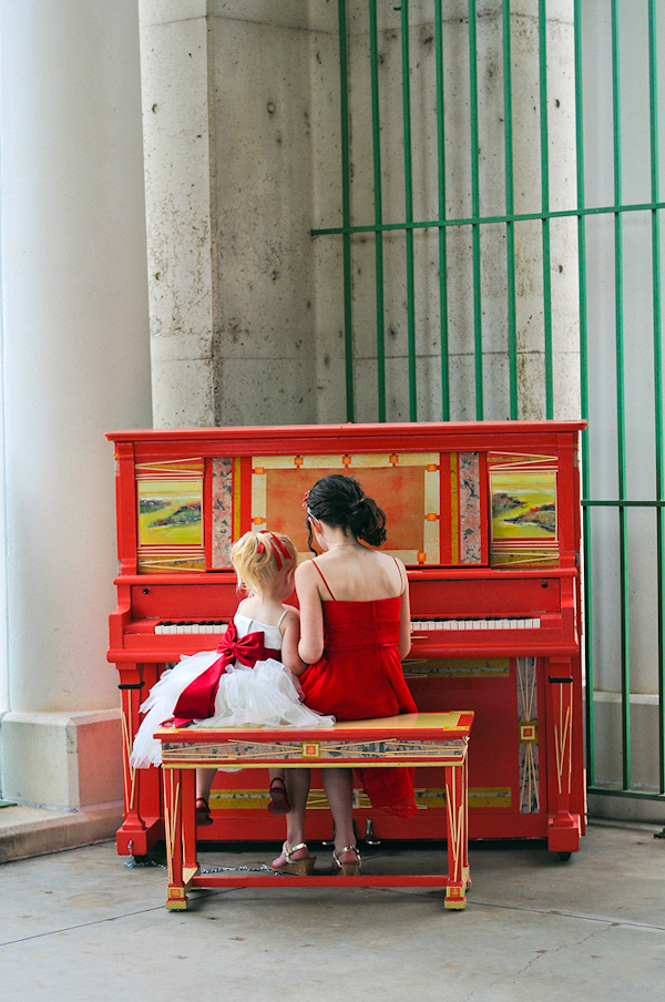 adorable photo of bridesmaid playing the piano with flowergirl - sweet wedding photo by top Minnesota wedding photographers Red Ribbon Studio