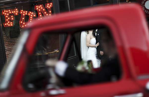 creative perspective photo of couple standing acrros the street with red truck driving through frame - genius alternative wedding portrait by Minnesota photographer Beau Peterson of BP Photo