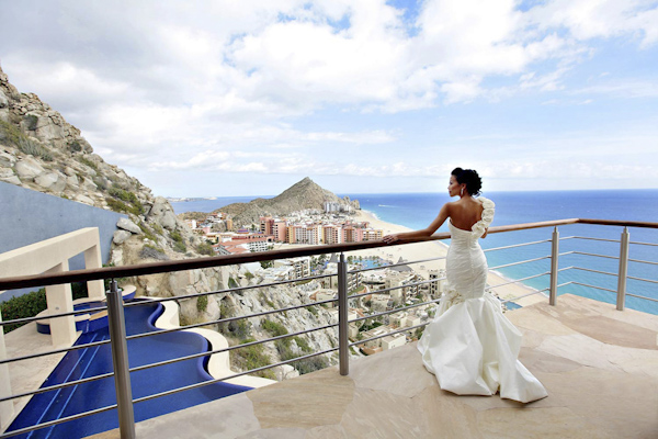 bride standing on balcony overlooking beautiful Cabo San Lucas Mexico - photo by top destination wedding photographers Chris plus Lynn photography