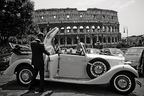 bride and groom getting into vintage convertible in front of Roman coliseum - photo by Rochelle Cheever of Rome Weddings Photography