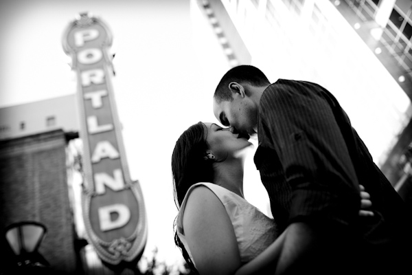 black and white photo of the happy couple kissing under Portland sign - engagement photo by top Portland, Oregon photographer Daniel Stark