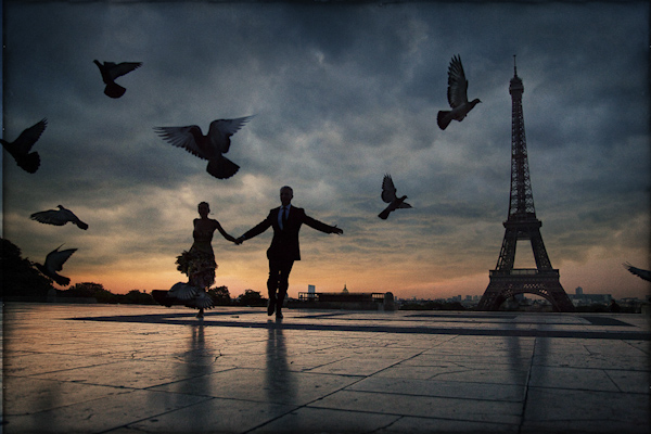 beautiful silhouette of couple holding hands, running through Eiffel Tower plaza at sunset - Paris wedding photo by top Florida based destination wedding photographer Adagion Studio
