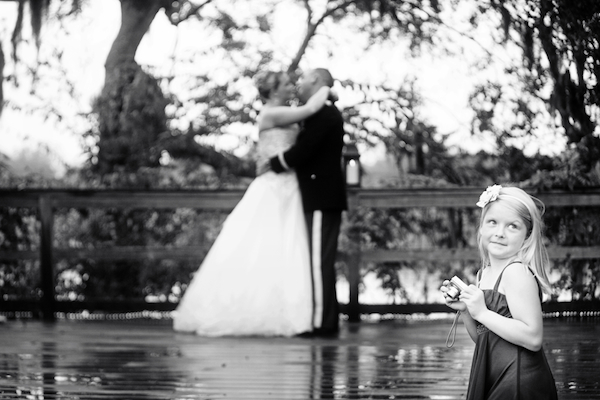 adorable wedding photo, by top South Carolina photographer Virgil Bunao, of a flower girl taking a photo of the happy couple