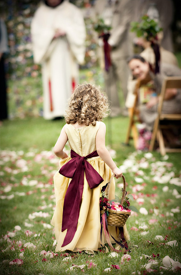 adorable wedding photo of a flower girl walking down the aisle by top North Carolina wedding photographers Woodward and Rick