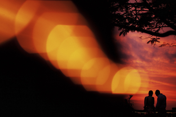 gorgeous, creative photo of couple silhouetted against orange sunset - Costa Rica resort wedding - photo by Denver based destination wedding photographer Otto Schulze