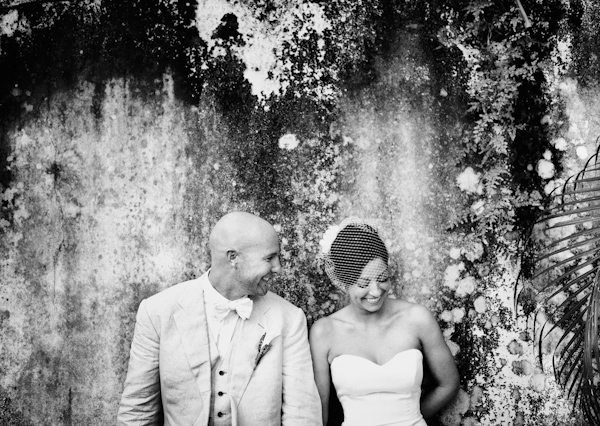 gorgeous black and white portrait of the happy couple in front of mossy wall - photo by Denver based destination wedding photographer Otto Schulze
