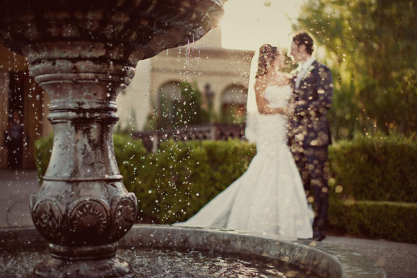 gorgeous wedding couple behind a fountain photo by Anika London Photography