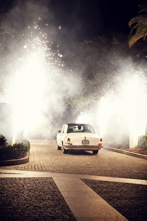 beautiful photo of couple riding away in car during grand firework wedding exit - photo by top Florida based photographers La Dolce Vita Studio