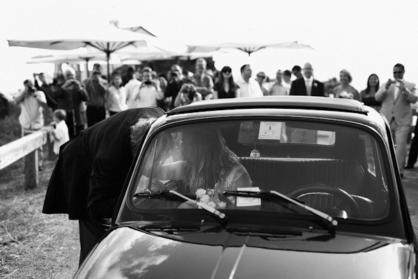 gorgeous black and white photo of the happy couple kissing in car during grand wedding exit - photo by top Italian wedding photographer Julian Kanz