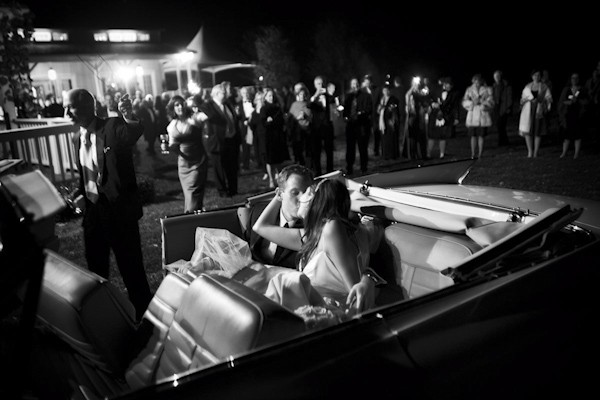 gorgeous black and white photo of the happy couple in convertible after grand wedding exit - photo by top photographers Holland Photo Arts