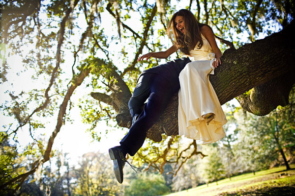 hilarious and heartwarming photo of a bride and groom climbing a tree by San Francisco based wedding photographers Ben Chrisman Photography