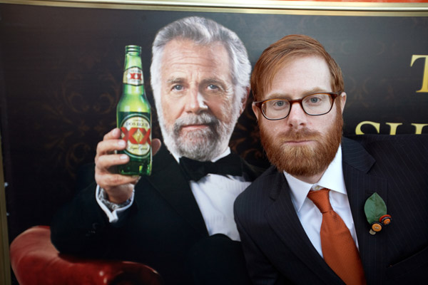 groom posed next to poster of Dos XX's Most Interesting Man in the World - hilarious wedding photo from top San Diego photographer Paul Barnett