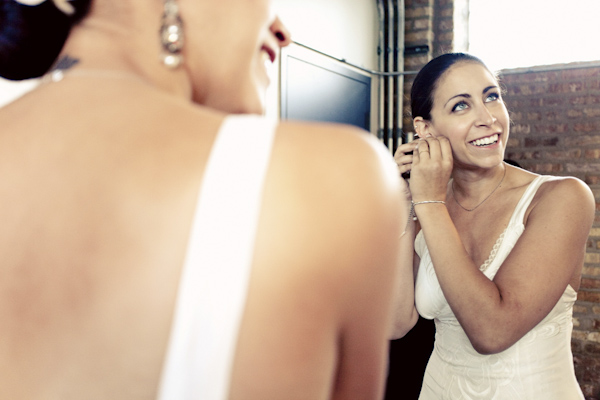 smiling bride looking in mirror, putting on earrings - getting ready before ceremony - hip, modern Jewish wedding at the Ravenswood Event Center in Chicago - photos by Studio 6.23