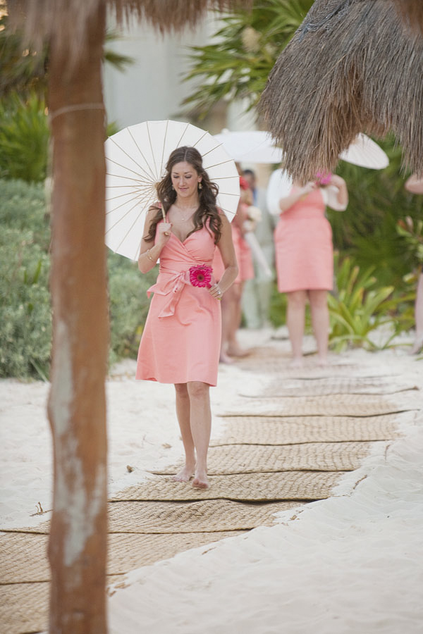 bridesmaid in salmon pink dress walking to ceremony with white parasol accessory - beach wedding - Riviera Maya, Mexico destination wedding - photo by Dallas based wedding photographer Jeremy Gilliam