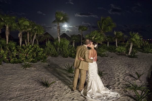gorgeous night shot of the happy couple kissing on the beach with palm trees in background - Riviera Maya, Mexico destination wedding - photo by Dallas based wedding photographer Jeremy Gilliam
