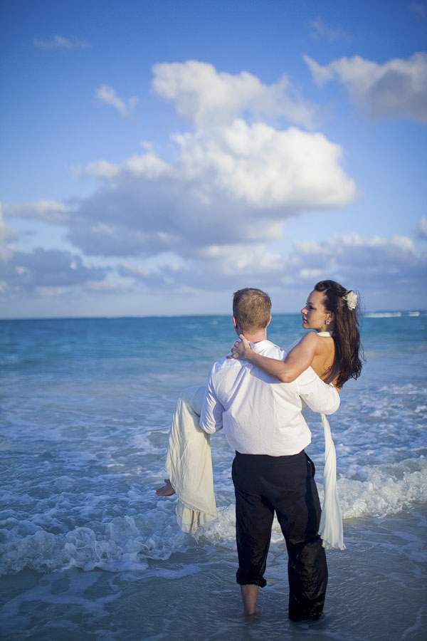 groom carrying bride on the beach - beautiful blue skies and water - Riviera Maya, Mexico destination wedding - photo by Dallas based wedding photographer Jeremy Gilliam