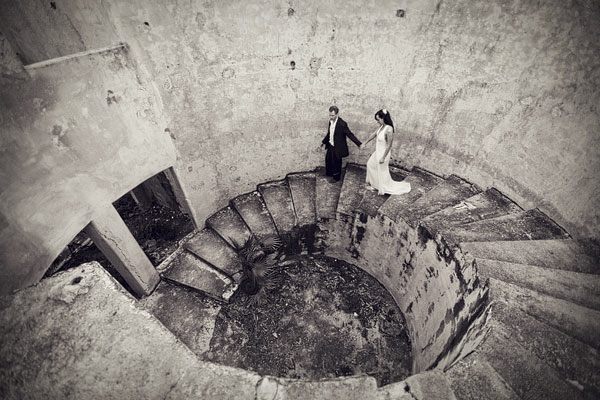gorgeous black and white photo of bride and groom walking down rock spiral staircase - Secrets Maroma Beach Resort, Riviera Maya, Mexico destination wedding - photo by Dallas based wedding photographer Jeremy Gilliam