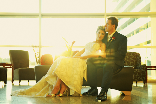 warm, backlit portrait of the happy couple sitting in front of bank of windows - fine art wedding photo by top Dallas based photographer Paul Ernest