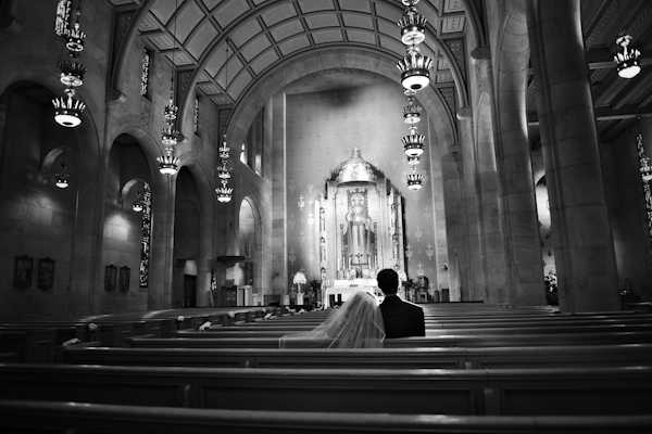 classic black and white photo of bride and groom sitting in Christ the King Catholic Church in Highland Park, Texas - fine art wedding photo by top Dallas based photographer Paul Ernest
