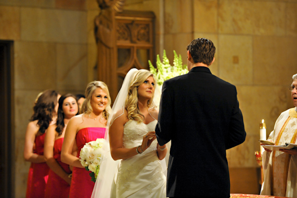 wedding ceremony moments - photo of bride putting ring on groom with bridesmaids watching - fine art wedding photo by top Dallas based photographer Paul Ernest