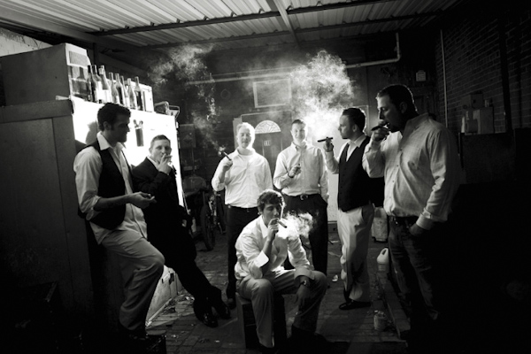 black and white photo of groom and groomsmen smoking cigars - fine art wedding photo by top Dallas based photographer Paul Ernest
