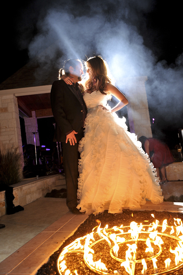 romantic portrait of the happy couple embracing in front of fire pit - fine art wedding photo by top Dallas based photographer Paul Ernest
