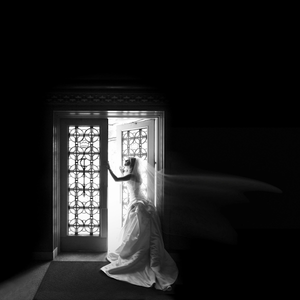 gorgeous black and white photo of bride standing in ornate doorway of Christ the King Catholic Church in Highland Park, Texas - fine art wedding photo by top Dallas based photographer Paul Ernest