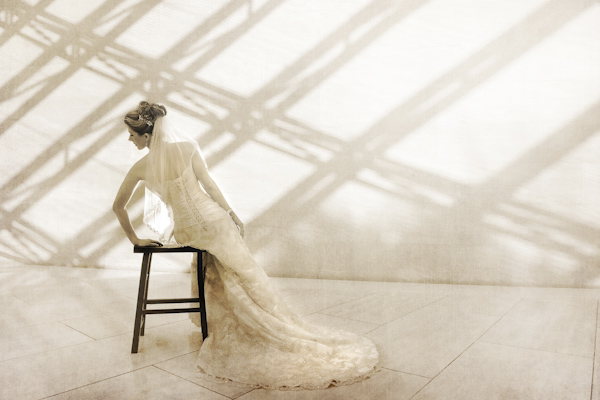 beautiful sepia toned portrait of bride gracefully leaning on chair - fine art wedding photo by top Dallas based photographer Paul Ernest