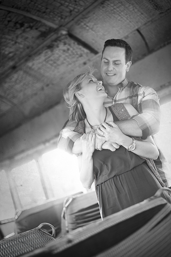 black and white photo of the happy couple kissing in antique train car - engagement photo by Houston based destination wedding photographer Adam Nyholt