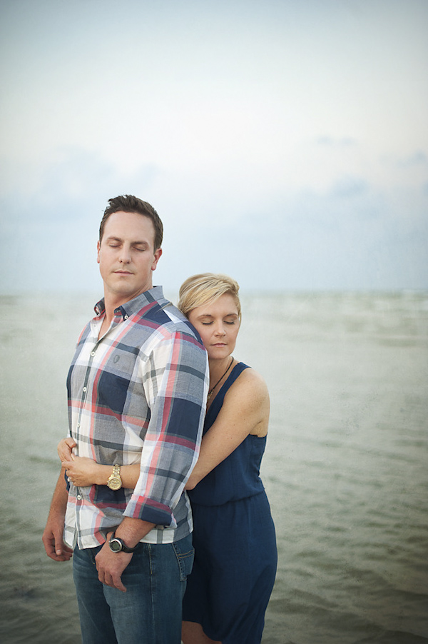 waterfront engagement shoot - the happy couple hugging with eyes closed on the beach - photo by Houston based destination wedding photographer Adam Nyholt
