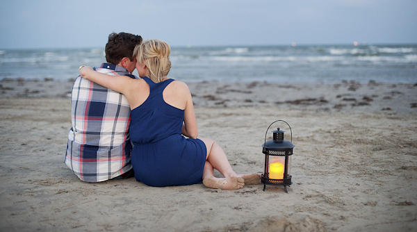 romantic waterfront engagement session - couple sitting on the beach at dusk with lantern - photo by Houston based destination wedding photographer Adam Nyholt